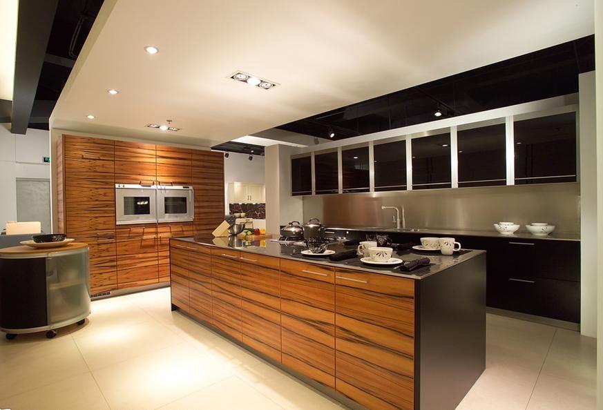 设计理念:现代科技的发展使工程技术人员有可能就厨房设计从功能上做一些改进工作。针对一些常见问题,如燃料、废气、油烟气、水蒸气的污染,主副食的贮藏、环境脏乱等,都做出了妥善解决,从而使厨房的环境得到极大改善,由油腻潮湿变为烹调、用餐的舒适高雅环境,开敞整洁,便于家庭主妇在烹饪的同时完成洗衣、照看孩子等杂务。现代厨房布局的主要特征包括按操作顺序设置设施,使操作者能按部就班地操作,从而减少往复交叉的重复做功;对废气的排放加以重视,保持屋内空气的清新,对人体的损害也降到了最小;通盘考虑设施尺度和协调。以增强室内空